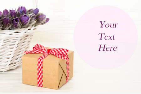 Gift and purple Anemon in basket over white background with space for your text. can be used for greeting card