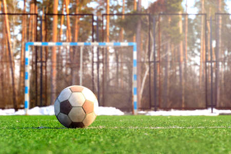 Old football ball on a grass. Used a lot. White soccer ball with no branding. Stock Photo - 122265321