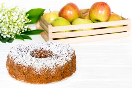 Apple Bundt Cake Sprinkled with Icing Sugar on white old wooden table with apples and spring flower of lily of the valley Stock Photo - 122265325