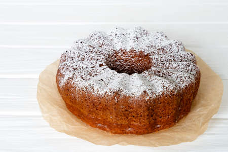 Homemade vanilla bunt cake on craft paper on wooden background Stock Photo - 122265326