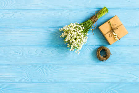 Gift box with spring flower on wooden desk Greeting concept background. top view, flat lay,