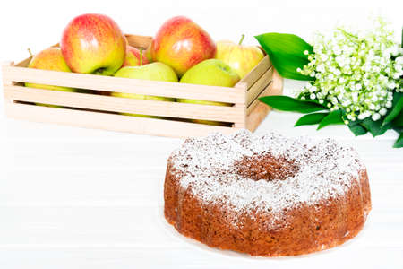 Apple Bundt Cake Sprinkled with Icing Sugar on white old wooden table with apples and spring bouquet