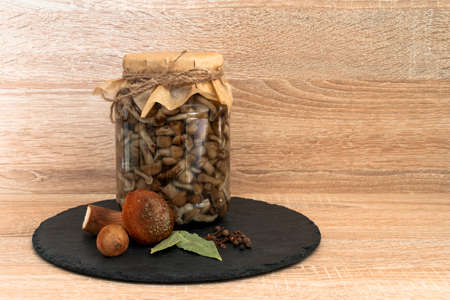 Marinated honey mushrooms in a bowl on the plateblack. On wooden background.