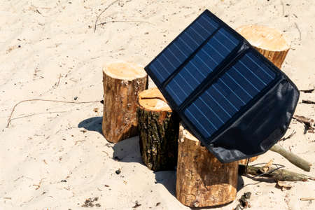 Portable solar panels lie on an wood and accumulate energy.