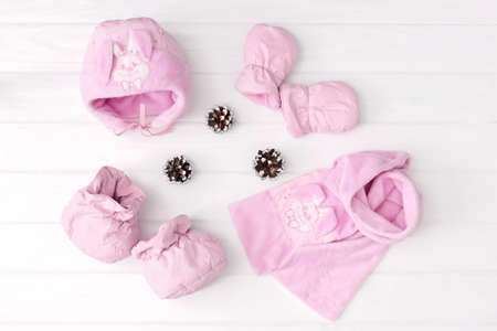 Set of childrens winter or autumn clothes. scarf, hat, mittens and booted on white background.