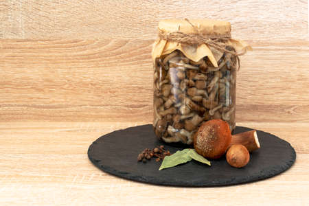 Marinated honey fungus mushrooms in a bowl on the plateblack. On wooden background. Stock fotó