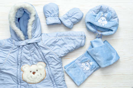 Autumn or winter fashion outfit. Baby boy blue set of clothing on white wooden background.