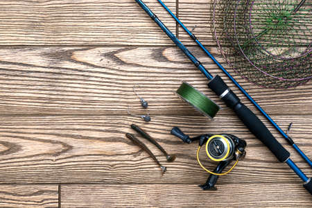 Fishing background. tackle - fishing spinning, hooks and lures on darken wooden background. Top view. Copy-space