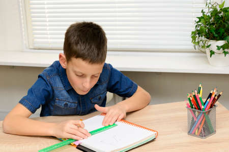 Boy draw in notebook. Child sitting at the desk home and doing his homework. School, children, education concept