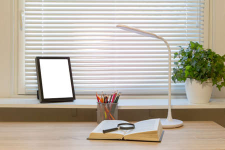 Work table with book, lamp and vase at home. Photo frame can be used mock-up