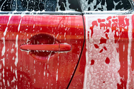 Manual car wash. Cleaning Car Using High Pressure Water. Washing with soap. Close up concept.