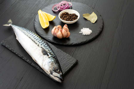 Fresh, raw mackerel with spices on a black concrete background