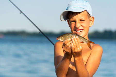 Happy smiling boy holding taken freshwater fish in hands against rod and river background Standard-Bild