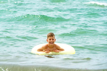 Happy smiling boy with inflattable swimming ring having fun in waves. Standard-Bild