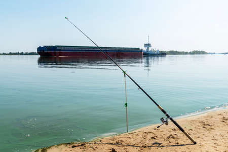 Fishing rod against tanker barge with grain on the Ukraine Dniepr river. Water logistic