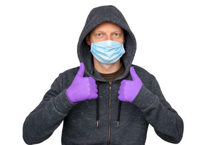 Caucasian man with beard protecting from the coronavirus with a mask and gloves over isolated background giving a thumbs up gesture Standard-Bild