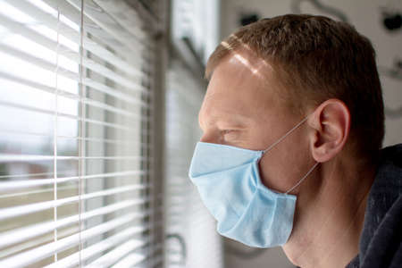 Man in a medical face mask looks out the window through the blinds. Quarantine during an epidemic.