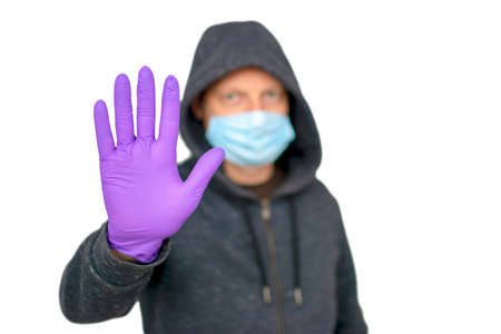 Healthcare and medical concept. Man in protective hygienic mask and gloves gesturing stop, warning of coronavirus epidemic, COVID-19 Standard-Bild
