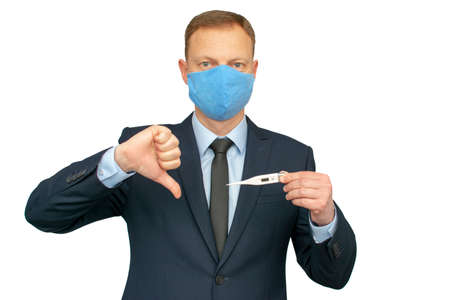 Young businessmanman giving thumbs down and wearing mask for protection from corona virus