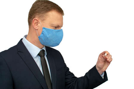 Businessman man in a medical mask looks at a thermometer.