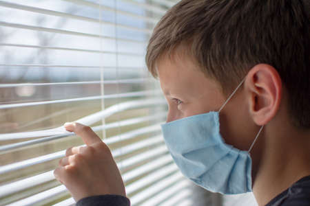 Boy in a medical face mask looks out the window through the blinds. Quarantine during an epidemic.