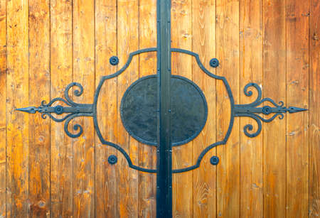 wooden gate with wrought iron ornament, closeup Standard-Bild