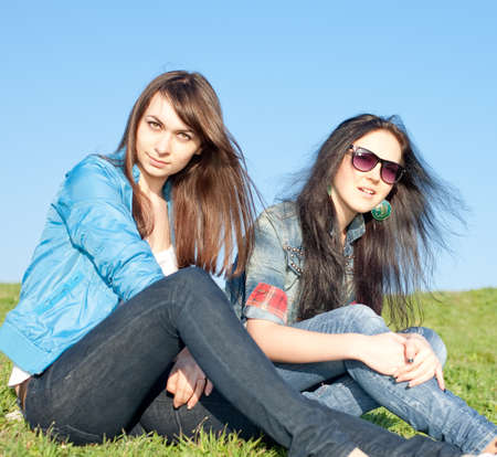 Two attractive brunettes in jeans are sitting on grass