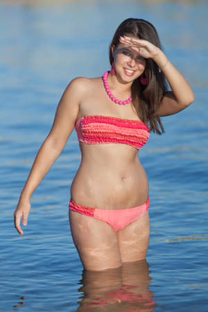 Attractive young woman at the sea. Brunette in pink swimwear knee-deep in water Stock Photo - 11893684