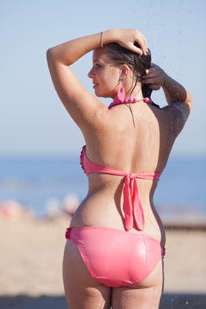 Nat meisje in bikini op de open lucht. Aantrekkelijke jonge vrouw in roze badpak droogt haar haar op het strand