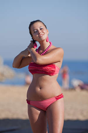 Attractive young woman in pink swimsuit dries her hair on the beach
