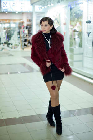 Retro Woman portrait. Young beautiful brunette in fur coat walking in the shop Stock Photo - 12037028