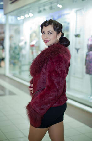 Retro Woman portrait. Young beautiful brunette in fur coat walking in the shop Stock Photo - 12037027