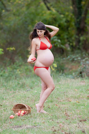 Pregnant woman in the autumn park. Expectant mother in red swimwear posing on open air photo