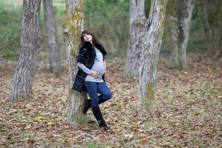 Pregnant woman in the autumn park. Expectant mother in monochrome coat in walnut grove Standard-Bild