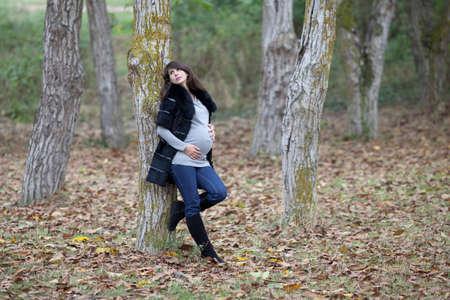 Zwangere vrouw in het najaar park. Aanstaande moeder in zwart-wit jas in Walnut Grove