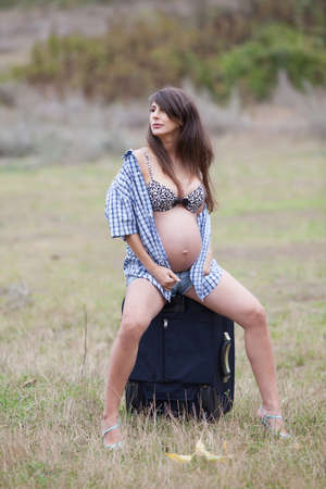 Pregnant woman in the autumn park. Expectant mother in unbuttoned checkered shirt and shorts sits on valise photo