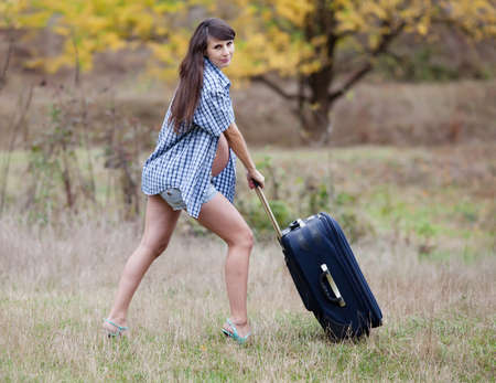 Pregnant woman in the autumn park. Expectant mother in unbuttoned checkered shirt and shorts with rolling suitcase photo