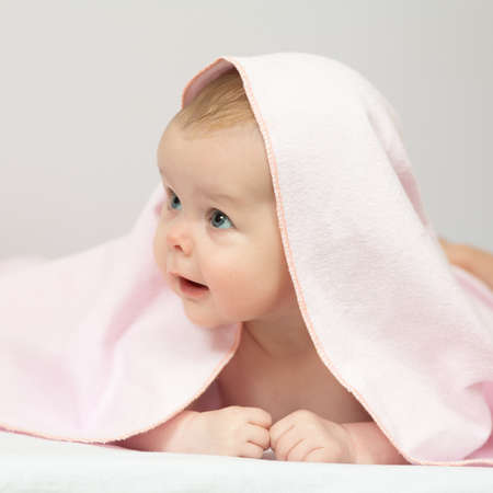 Charming baby. Beautiful baby under pink blanket Фото со стока