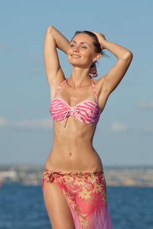 Meisje bij de zee. Aantrekkelijke jonge vrouw is die zich voordeed op de achtergrond van de zee. Dame in roze zwembroek met opgeheven armen op het strand