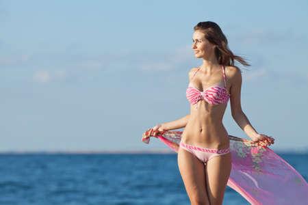 Meisje bij de zee. Aantrekkelijke jonge vrouw op de achtergrond van zee. Lady in roze zwembroek op het strand