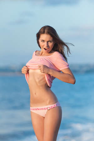 Girl at the sea. Attractive young woman showing her sexy tummy on background of sea. Lady in pink blouse and pink swimming trunks is undressing on open air Stock Photo - 12152266