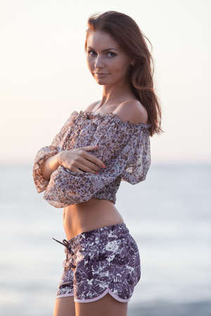 Lady at the sea. Attractive young woman in shorts and blouse on background of sea. Girl girl with arms folded looking at camera photo