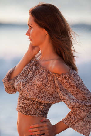 Lady at the sea. Attractive young woman in shorts and blouse on background of sea. Girl looking away photo