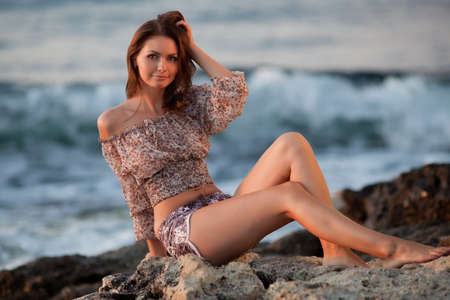 Lady at the sea. Attractive young woman in shorts and blouse on background of sea. Barefoot girl sitting on rock photo