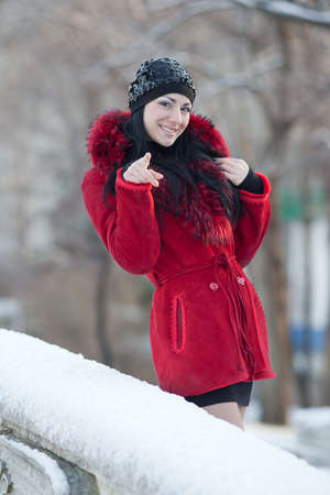 Beautiful young woman at winter. Young beautiful brunette in red standing in the winter park looking at camera smiling photo