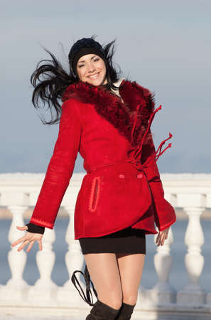 Beautiful young woman at winter. Attractive brunette in red jumping in the winter park photo