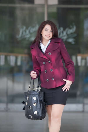 건물의 배경에 매력적인 비즈니스 여자입니다. 회색 하루에 밖에 서 산책하는 귀여운 비즈니스 우먼