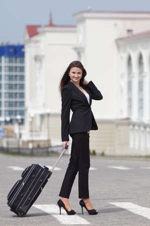 Brunette with valise on open air Young woman in black suit with rolling suitcase walking along the crosswalk photo