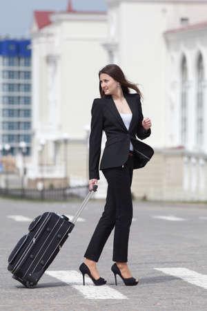 Brunette met valies op de open lucht Jonge vrouw in zwart pak met rollende koffer een wandeling langs het zebrapad