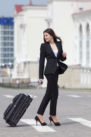 valise: Brunette with valise on open air Young woman in black suit with rolling suitcase walking along the crosswalk Stock Photo